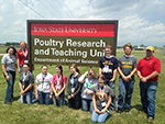Students posing near Poultry Farm Sign